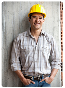 Smiling construction worker leaning against wall