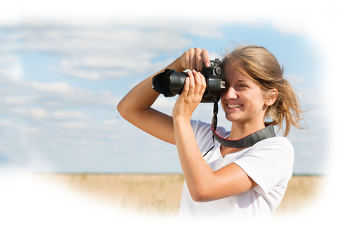 Girl holding a camera in a field